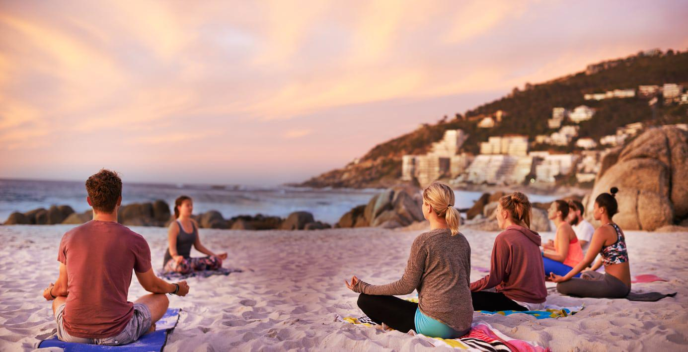 Group-of-multicultural-people-meditating-at-the-beach-1